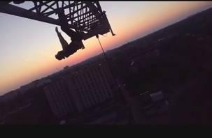 На видео сняли смолянина, висящего вниз головой на башенном кране